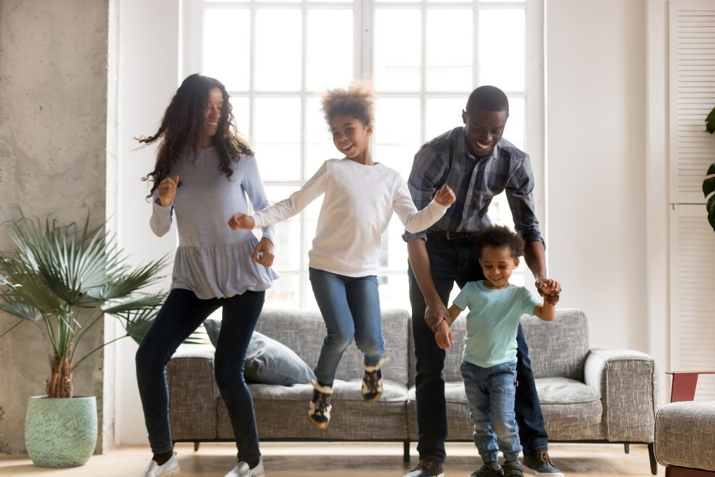 Photo of family jumping and dancing in the living room, two children and two adults looking very happy together. Hope and healing is possible in Northern Virginia with postpartum depression treatment