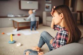 Photo focused on a woman who with her hand on her head and eyes closed, wearing ripped jeans and a plaid shirt, sitting in the living room with her baby playing near her. Postpartum depression and anxiety can be treated with help from our Northern Virginia women's mental health therapists.